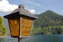Street Old Vintage Square-shaped Lantern With Brown Glass Against The Backdrop Of Green Mountains And Blue Sky With Clouds, Used As A Background Or Texture