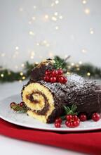 Dolce Natalizio Tradizionale. Buche De Noel, Tronchetto Di Natale Con Crema Al Cioccolato E Ribes Su Sfondo Bianco. Decorazioni Natalizie.