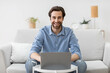 Man at laptop computer works online and smiles at home