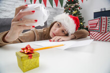 Sad Young Woman In Santa Hat Looking At Empty Piggy Bank. Christmas Gifts Expenses And Overspending Concept.