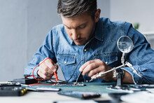 Focused Repairman Holding Sensors Of Multimeter On Disassembled Part Of Mobile Phone On Blurred Foreground