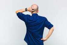 Bald Man Feeling Clueless And Confused, Thinking A Solution, With Hand On Hip And Other On Head, Rear View