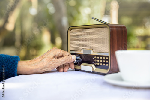 Papel de parede Senior woman hand turning knob on vintage radio in backyard.