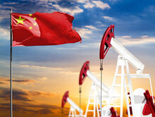 Oil Rigs Against The Backdrop Of The Colorful Sky And A Flagpole With The Flag Of China. The Concept Of Oil Production, Minerals, Development Of New Deposits.