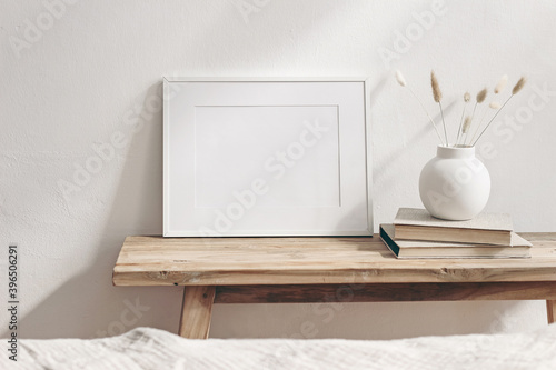 Fototapeta Winter still life. Horizontal white frame mockup on vintage wooden bench, table. Modern white ceramic vase with pine tree branches, Christmas paper ornaments and books. White wall background. obraz