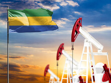 Oil Rigs Against The Backdrop Of The Colorful Sky And A Flagpole With The Flag Of Gabon. The Concept Of Oil Production, Minerals, Development Of New Deposits.