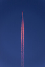 Airplane Making Colorful Contrails In The Sky