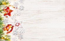Snowflakes And Christmas Decorations With Green Pine Twigs And Yellow Festive Lights On White Painted Wood