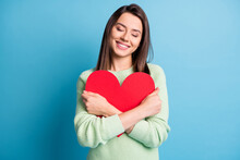 Photo Of Charming Young Lady Embrace Red Paper Heart Closed Eyes Wear Green Pullover Isolated Blue Color Background