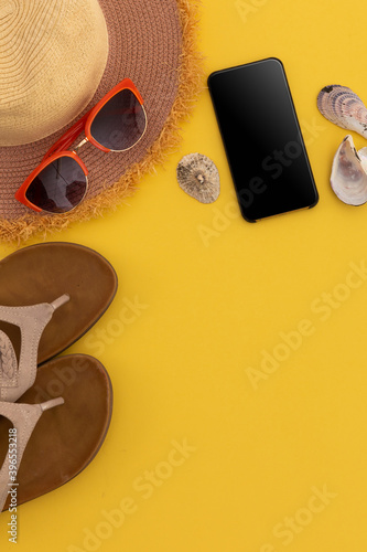 Sunglasses, flip flops, sunhat, shells and smartphone on yellow background