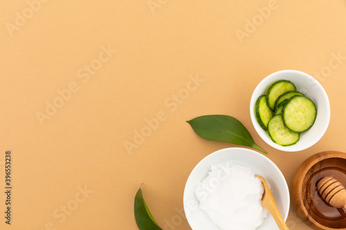 Bowls with yoghurt, cucumber and dressing on yellow background