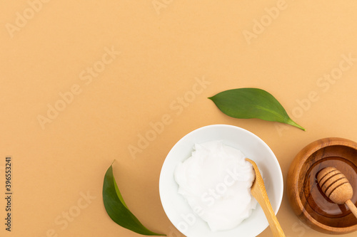 Bowls with yoghurt and dressing on yellow background