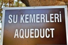 Signpost Direction To Aqueduct,. Ancient Water Supply At The Ruin Ancient City Of Perge, Near Antaliya, Turkey, Where Tourist Related Signs Use A Brown Background With White Letters.