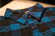 Collar Of A Dark Blue Plaid Shirt With Black Buttons