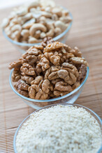 Three Glass Bowls With Walnut, White Sesame Seeds And Cashew Nuts On A Bamboo Napkin.