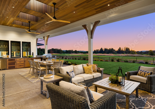 Papel de parede Luxury home exterior at sunset: Outdoor covered patio with kitchen, barbecue, dining table, and seating area, overlooking grass field and trees