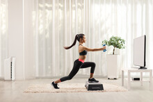 Female Exercising Step Aerobic With Small Weights In Front Of A Tv At Home