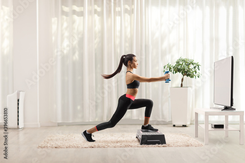 Fototapeta Female exercising step aerobic with small weights in front of a tv at home obraz