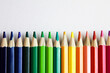 colored pencils lie in a row on a white background