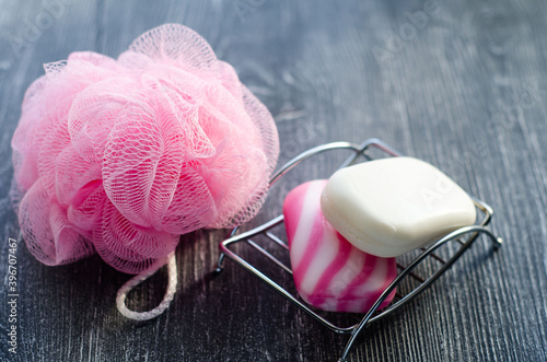 Fotomural Soap of different colors on  metal stand and  pink washcloth on  gray background