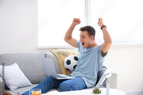 Canvas Happy man after winning his sports bet at home