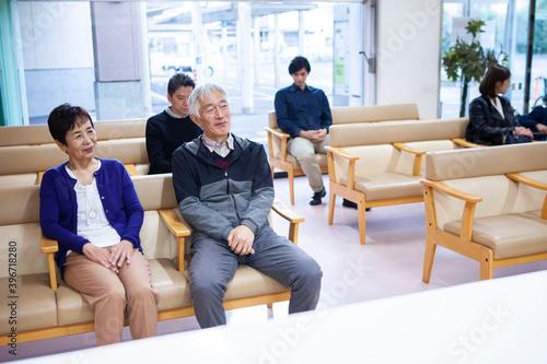 病院の待合室で待つ人々 Fototapet