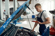 Mechanic doing diagnostic of engine with digital tablet
