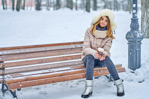 Fototapeta Attractive woman sits on a bench in a winter park. She is dressed warmly. In hand is a paper cup with hot coffee. copy space obraz na płótnie