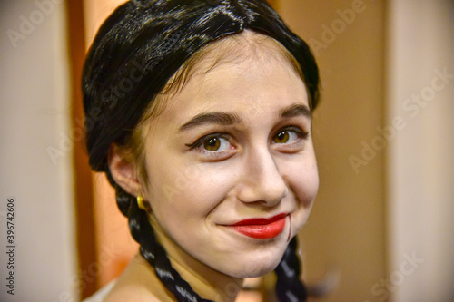 Portrait of a girl in a black wig and makeup for a Halloween celebration Fototapeta