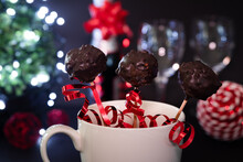 Not Perfect Shape, Three Chocolate Cake Pops Handmade In White Mug. Selective Focus. Black Background, Black Table, Red Christmas Season Decoration, Wine Glasses, Fairy Lights