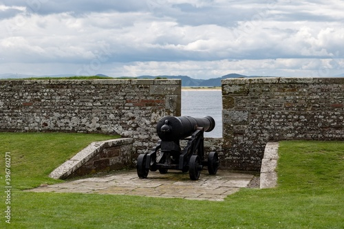 Leinwand Poster Stone brick protective wall and war cannon at barracks complex in historical For