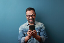 Middle Aged Man Of Indian Origin Looking At His Mobile Phone With A Surprise