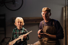 A Young Carpenter Dad And His Cute Blond Son Made A Gun Out Of Wood And Show It, They Are Happy, Sitting In The Carpenter's Workshop On The Table