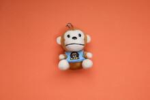 A Soft Toy Monkey Isolated On Orange Background