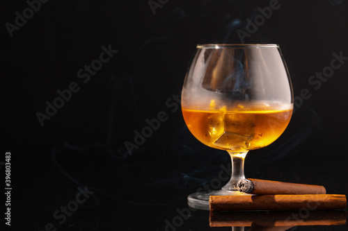 Glass of whisky and lighted cigar on black background Wallpaper Mural