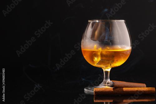 Valokuvatapetti Glass of whisky and lighted cigar on black background