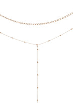 Cropped Close-up Shot Of Golden Multirow Necklace Consists Of Simple Curb Chain And Thin Chain With Glossy Metal Beads. The Elegant Jewelry Set Is Isolated On The White Background.