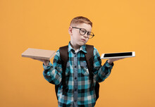 Confused Schoolboy Holding Digital Tablet And Book