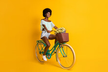 Photo Portrait Full Body View Of Girl Riding Bicycle Isolated On Vivid Yellow Colored Background