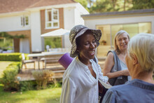 Happy Senior Women Friends With Yoga Mat In Summer Garden
