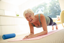 Portrait Happy Senior Woman Practicing Plank Pose On Yoga Mat At Home