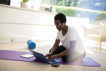 Woman Working And Exercising On Yoga Mat At Home