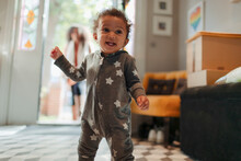 Cute Happy Baby Girl In Star Pajamas At Home
