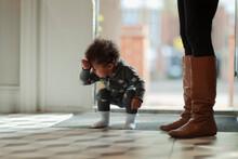 Cute Baby Girl In Pajamas Crouching At Front Door