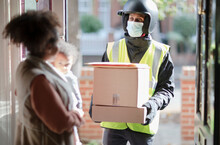 Woman Receiving Parcels From Delivery Man In Face Mask At Front Door