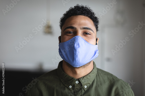 Portrait of middle eastern man wearing face mask against grey background