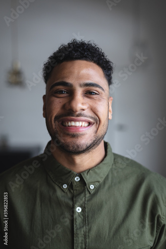 Portrait of middle eastern man smiling against grey background