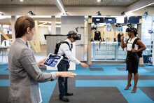 Woman Guiding Colleagues Through VR Immersive Experience
