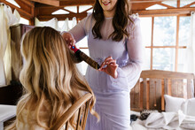 Maid Of Honor Curling Hair For Bride On Wedding Day
