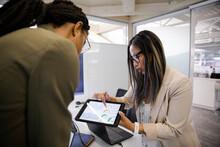 Businesswomen Discussing Statistics On Digital Tablet In Office